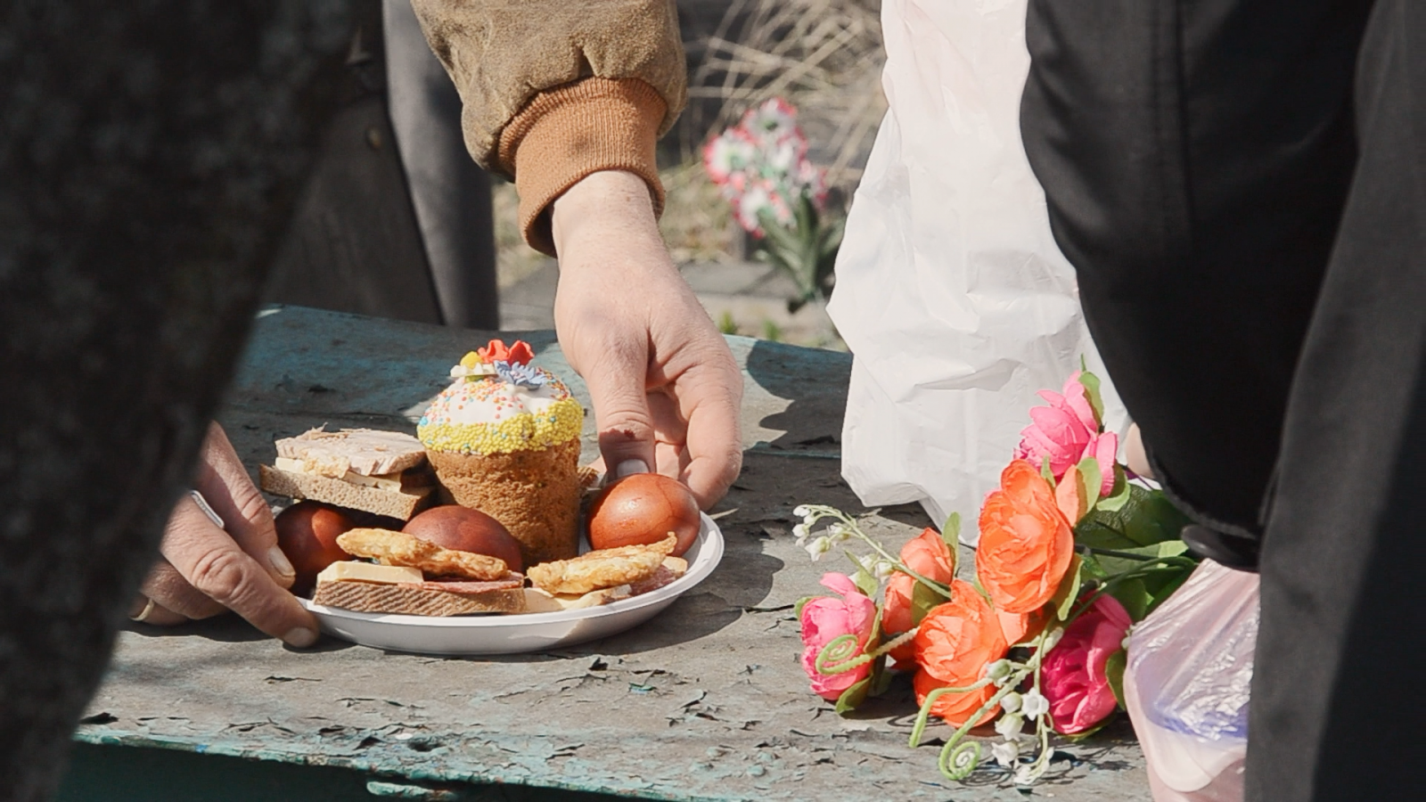 eng: Hands lower a plate with Easter cake, Easter eggs and cookies next to a bouquet of plastic flowers
