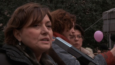 Mature brown-haired woman speaks into a microphone on the background of other women
