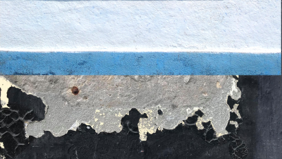 Abstract painting with yellow-gray, gray, white, blue horizontal stripes on a chipped black concrete wall