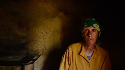 A woman dressed in a yellow shirt and a green handkerchief in the semi-darkness of her own hut