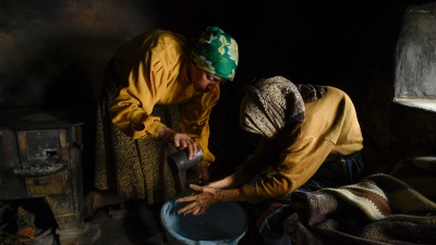 Two elderly women are sitting in the dark, dressed in yellow. Woman in a green handkerchief washes the hands of a woman in a brown handkerchief.